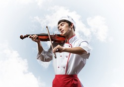 Young male chef playing violin on blue sky background. Handsome chef in white hat and red apron standing with music instrument. Creative culinary performance. High cooking skills concept