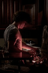 Young male cooking at night in a stove