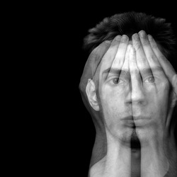 Young male covering his face with his hands over black background with copyspace.