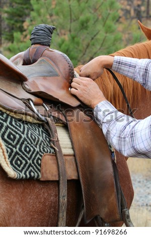 Young male cowboy adjusting the saddle on his horse