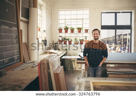 Young male craftsman standing with his hands in his pockets in his workshop and smiling at the camera in a way that is both confident and comfortable