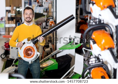 Young male customer examining leaf blowers in garden equipment shop