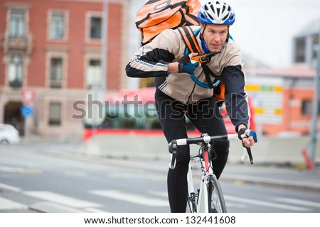 Young male cyclist with courier delivery bag riding bicycle on street