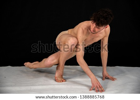 Young male dancer with beard, sitting in gymnastic pose with moving leg and hand positions. The attractive young man shows modern dance poses, dancing in the studio against a black background. #1388885768