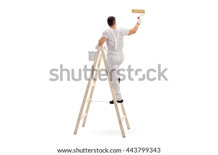 Young male decorator painting with a paint roller climbed up a ladder isolated on white background #443799343