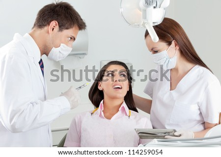 Young male dentist looking at nurse comforting patient in clinic
