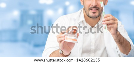 Young male dentist showing toothbrush and denture in dental clinic. Selective focus at the toothbrush. #1428602135