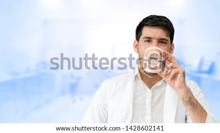 Young male dentist showing toothbrush and denture in dental clinic. Selective focus at the toothbrush. #1428602141