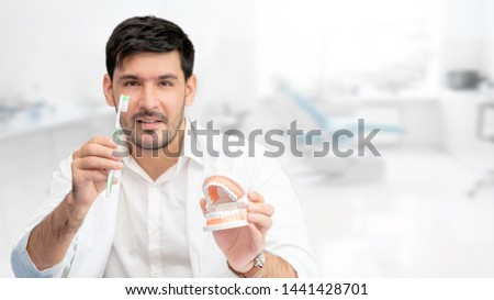 Young male dentist showing toothbrush and denture in dental clinic. Selective focus at the toothbrush.