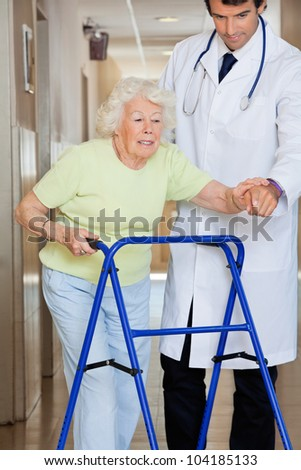 Young male doctor showing way to the patient using walker