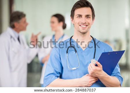 Young male doctor with colleagues at doctor\'s office.