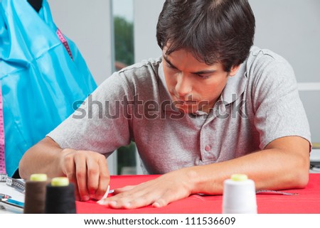 Young male dressmaker drawing line on a red fabric with chalk - stock photo