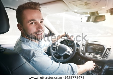 Young male driver behind the wheel. Sharing economy service or taxi driver concept