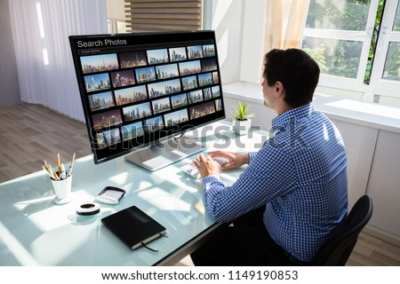 Young male editor searching photos on computer in office
