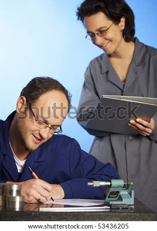 Young male engineer in blue overall recording precision measurement data of metal parts in screw micrometer and assistant in background watching him, isolated on blue background.