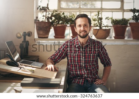 Young male entrepreneur sitting in the office space of his design studio looking confidently at the camera