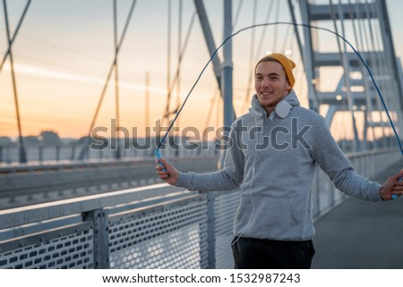 Young male excersicing outside on bridge. Rope skipping. Jumping rope workout. Cardiovascular workouts - Stock Image