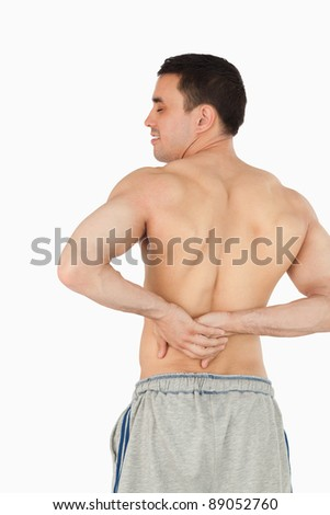 Young male experiencing back pain against a white background