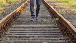 Young Male Feet Walking In Between Rusty Abandoned Railroad Tracks At Sunset.