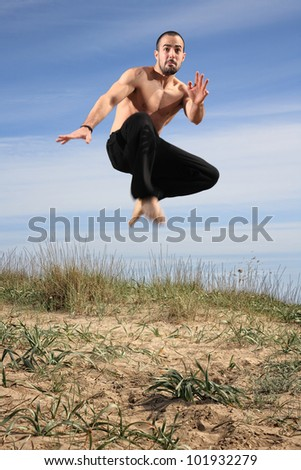 young male fighter exercising on a sand hill motion blur