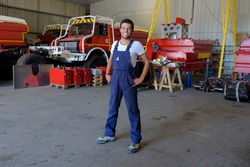 young male firetruck mechanic posing