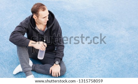 Young male fitness trainer in a gray suit drinking water from his bottle after a fat burning morning street workout. Concept of water balance replenishment during workouts #1315758059