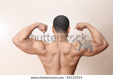 Young male flexing back and arm muscles