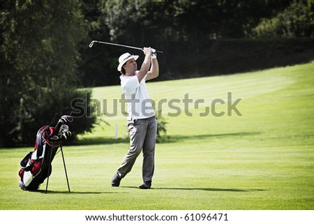 Young male golf player pitching at golf course with golf bag standing aside.