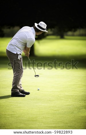 Young male golf player putting on green with dark forest in the background, usable as free space for text.