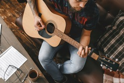 Young male guitarist hipster indoors playing guitar top view close-up inspired