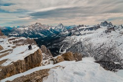 Young male hiker alpinist with backpack on holiday in amazing dolomites landscape - Travel winter destination, Cortina snowy mountain in cloudy sky day