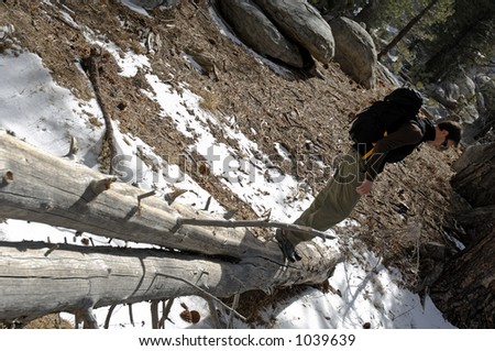 Young male hiker crossing frozen stream on log.