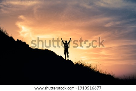 Young male hiker standing on a mountain feeling happy and inspired. Adventure, mental strength, and physical health concept. ストックフォト ©