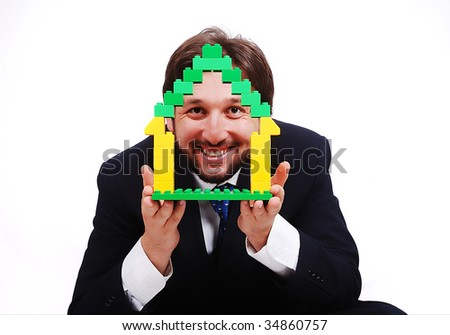 Young male holding homes made by cubes
