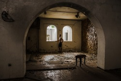 Young male in a dark blue shirt staring outside a windown in an abandoned building