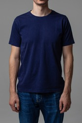 Young male in blank navy t-shirt, front view. Design men t shirt template and mock-up for branding or print.