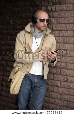 young male in khaki jacket listen to his music, lean against wall, outdoor shoot