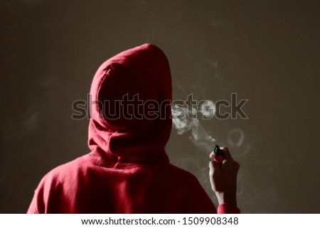 Young male in red hoodie vaping smoking, blows a single smoke ring while holding an electronic cigarette in hand, isolated rear view #1509908348