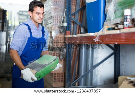 young male in uniform is choosing cement in the building store room