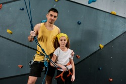 Young male instructor and active girl in safety equipment looking at camera, standing against artificial training climbing wall. Concept of sport and rock climbing. Selective focus. Horizontal shot