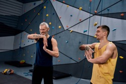 Young male instructor and middle aged man smiling, warming up bodies, while preparing for climbing in bouldering center. Concept of sport life, healthy active lifestyle