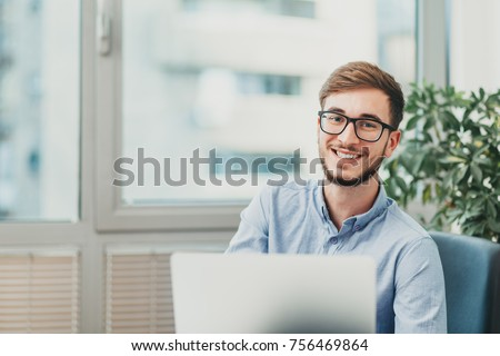 Young male intern with glasses working on laptop and smiling at the camera Stockfoto ©