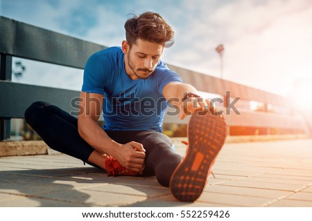 Young male jogger athlete training and doing workout outdoors in city #552259426