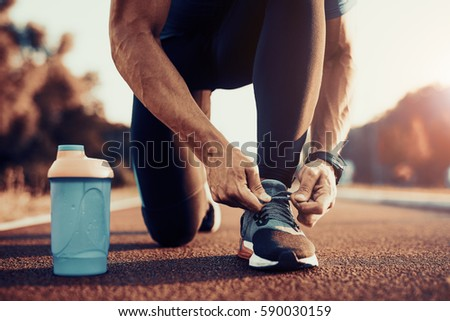 Young male jogger athlete training and doing workout outdoors in city. #590030159