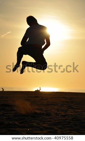 Young male jumping on a beach with an evening sun