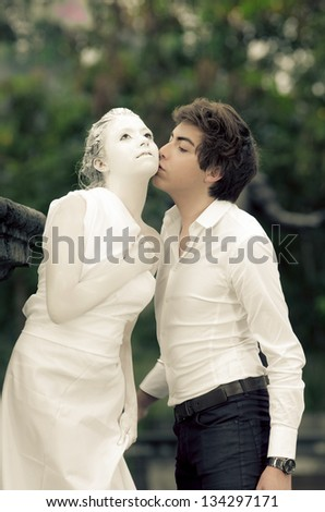 Young male KISSING at a young female MODEL DRESSED AS A carved statue