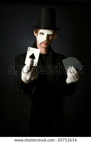Young male magician playing with cards