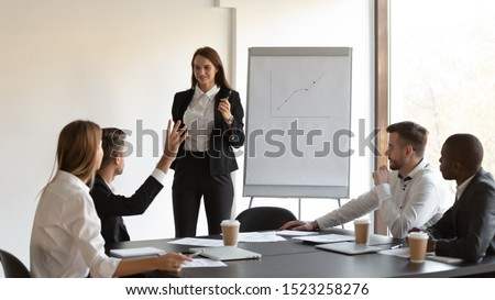 Young male manager raising hand to ask question about growth trends to confident female presenter. Smiling business woman trainer explaining working issues to mixed race group of motivated employees.