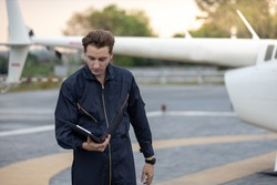 Young male mechanic inspecting a helicopter before taking off. He is holding his checklist in his hand. He wear full body jumpsuit. There is a helicopter behind him.