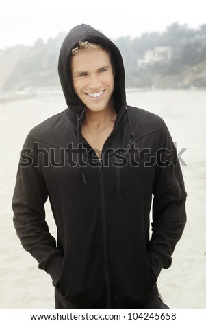 Young male model outdoors in stylish active clothing with bright happy smile - stock photo